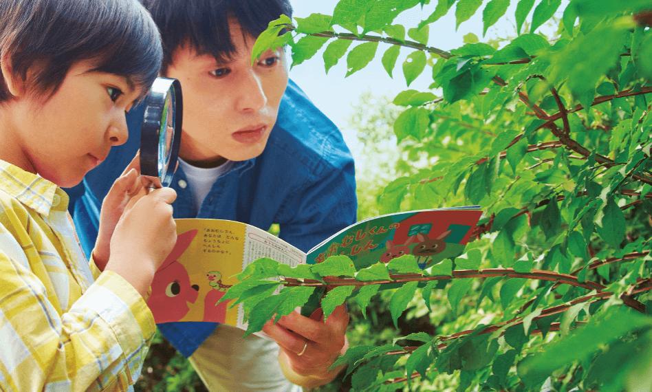 虫眼鏡で植物を見ている男の子