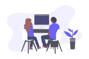 パソコンの前に座る男女